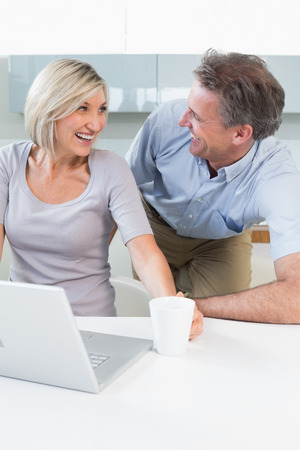 Happy casual couple using laptop in the kitchen at home photo