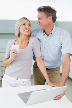 Happy loving couple with laptop in the kitchen at home photo
