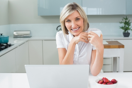 Portrait of a casual happy woman with coffee cup and laptop in the kitchen at home photo