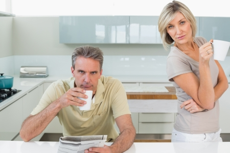 Portrait of serious couple with coffee cups and newspaper in the kitchen at home photo