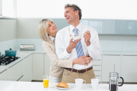 Woman embracing a happy man from behind in the kitchen at home photo