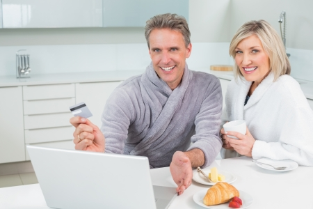 Portrait of a couple in bathrobes doing online shopping in the kitchen at home photo