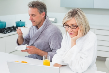 Couple in bathrobes with coffee and juice using laptop in the kitchen at home photo
