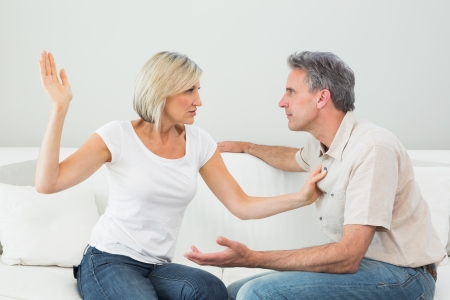 Angry woman about to slap a man while having a fight in the living room at house photo