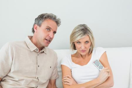 pareja viendo tv: Pares serios viendo la televisi�n en la sala de estar en casa