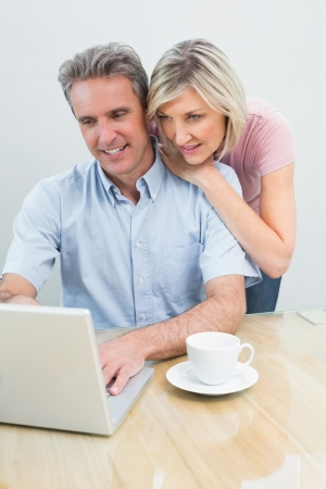 Concentrated content casual couple using laptop at home photo