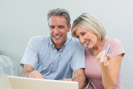 Cheerful couple doing online shopping with debit card and laptop in the living room at home photo