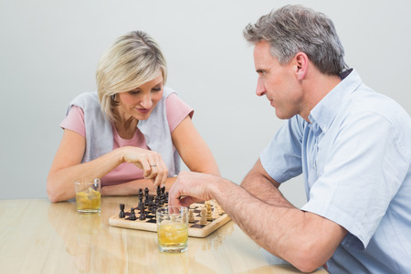 Happy woman and man playing chess at home photo