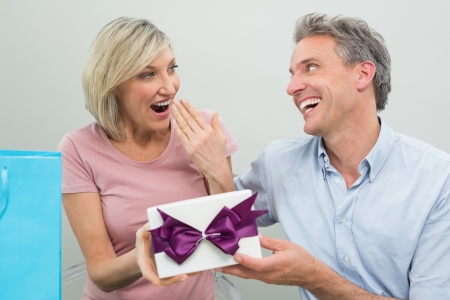 gifting: Happy man giving a surprised woman a birthday gift at home