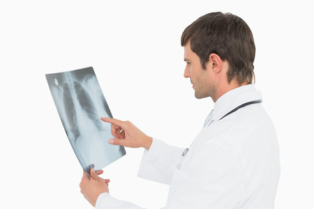 Side view of a concentrated male doctor looking at x-ray picture of lungs over white background photo
