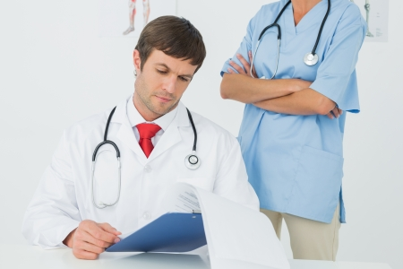 Concentrated male doctor reading reports beside a nurse in the medical office photo