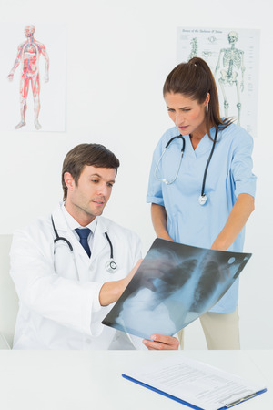 Male doctor and female surgeon examining x-ray in a medical office photo