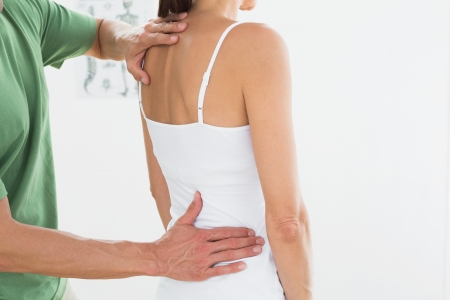 Side view of a male physiotherapist examining womans back in the medical office Stock Photo