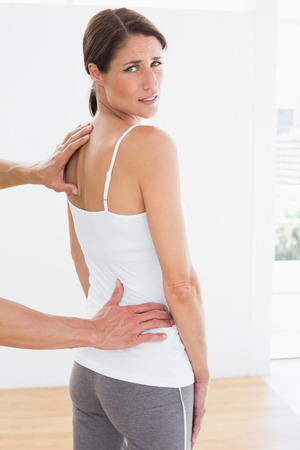 back muscles: Rear view of a male physiotherapist examining womans back in the medical office