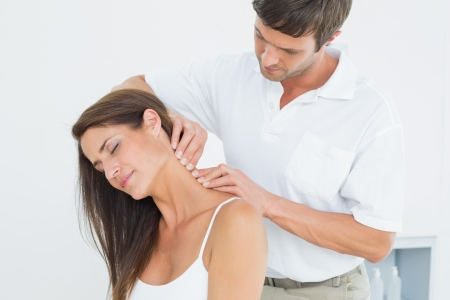 Male chiropractor massaging a young womans neck in the medical office photo