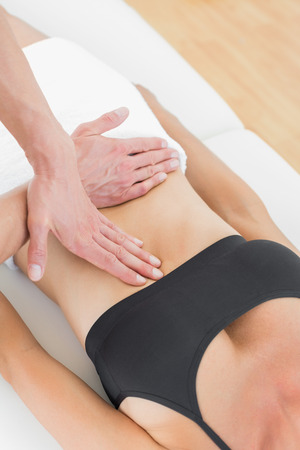 Close-up mid section of a physiotherapist massaging womans body in the medical office photo