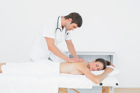 Male physiotherapist massaging womans back in the medical office photo