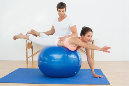 Physical therapist assisting young woman with yoga ball in the gym at hospital Foto de archivo