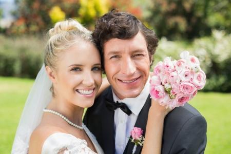Attraktive Braut und Bräutigam umarmt und lächelnd in die Kamera in der Landschaft Standard-Bild - 25505458