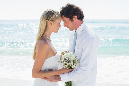 Loving couple on their wedding day at the beach photo
