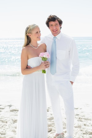 Cute happy couple on their wedding day at the beach photo
