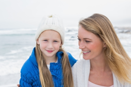 Portrait of a cute young girl with smiling mother relaxing at the beach photo