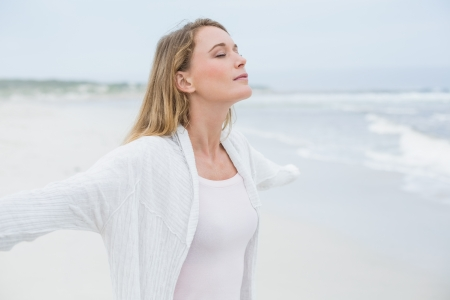 Side view of a peaceful casual young woman with eyes closed at the beach Reklamní fotografie