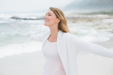 Peaceful casual young woman with eyes closed at the beach
