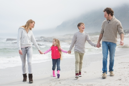 Full length of a happy family of four walking hand in hand at the beach photo