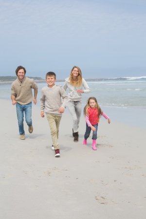 Full length portrait of a happy family of four running at the beach photo