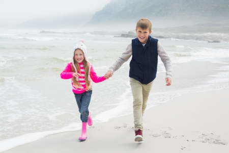 Full length of a happy brother and sister walking hand in hand at the beach photo