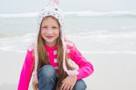 escapism: Portrait of a cute little girl in warm clothing at the beach