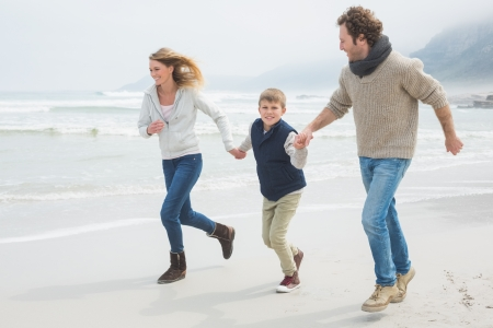 Full length of a happy family of three running on sand at the beach