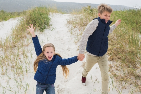 Happy brother and sister running hand in hand at the beach photo