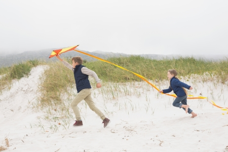 Full length side view of cheerful kids running with kite at the beach photo