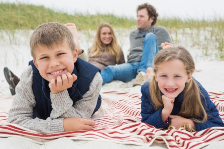 Portrait of happy siblings with parents sitting in background at the beach photo