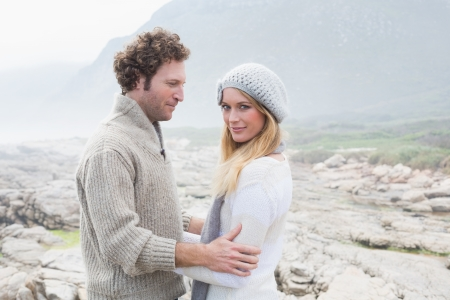 Side view of a romantic young couple standing together on a rocky landscape photo