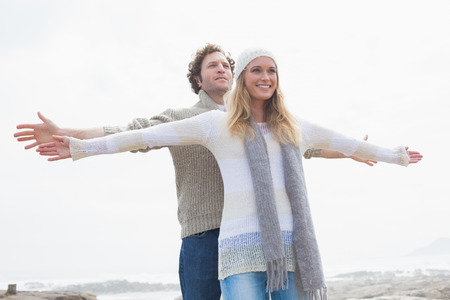 arms  outstretched: Happy casual young woman and man stretching hands out against the sky Stock Photo