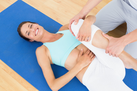 Physical therapist examining a happy young woman's leg at the hospital gym photo
