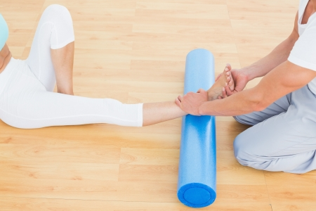 Physical therapist examining a young womans leg at the hospital gym photo