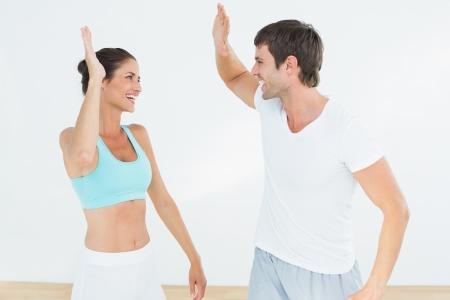 body slim: Enthousiaste ajustement jeune couple donnant la haute cinq dans le studio de remise en forme