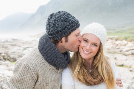 enamorados besandose: Hombre joven que besa a una mujer hermosa en un paisaje rocoso Foto de archivo
