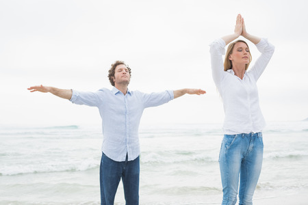 Peaceful casual young woman and man with eyes closed at the beach photo