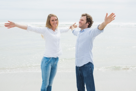Happy casual young woman and man stretching hands out at the beach photo