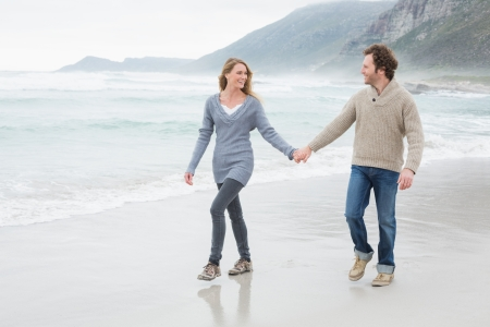 Full length of a happy casual young couple holding hands and walking at the beach photo