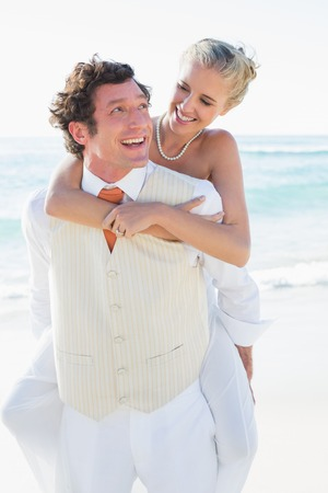 Smiling bride getting a piggy back from husband at the beach photo
