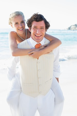 Happy bride getting a piggy back from husband at the beach photo
