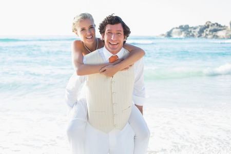 Happy bride getting a piggy back from husband smiling at camera at the beach photo