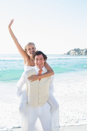 Waving bride getting a piggy back from husband smiling at camera at the beach photo