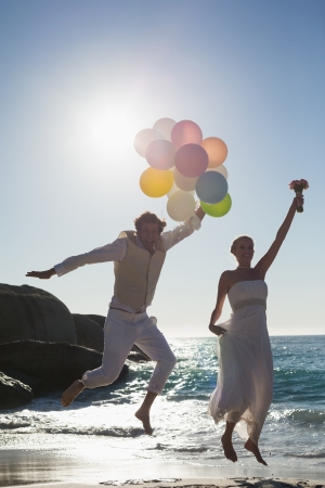 Groom holding balloons and bride holding bouquet jumping at the beach photo